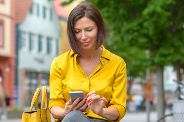 Attractive woman typing a message on her mobile Attractive woman in colorful yellow shirt sitting typing a message on her mobile phone on a bench in an urban street with a happy smile midsection stock pictures, royalty-free photos & images
