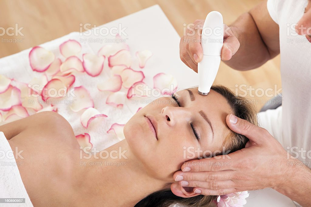 Attractive woman undergoes facial treatment royalty-free stock photo