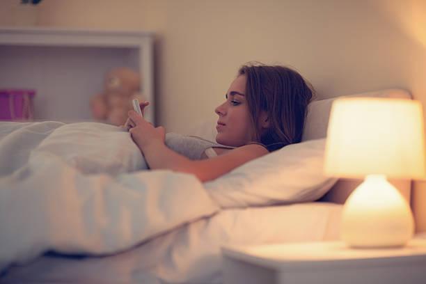 attraktive frau mit ihrem smartphone - nachttischleuchte touch stock-fotos und bilder