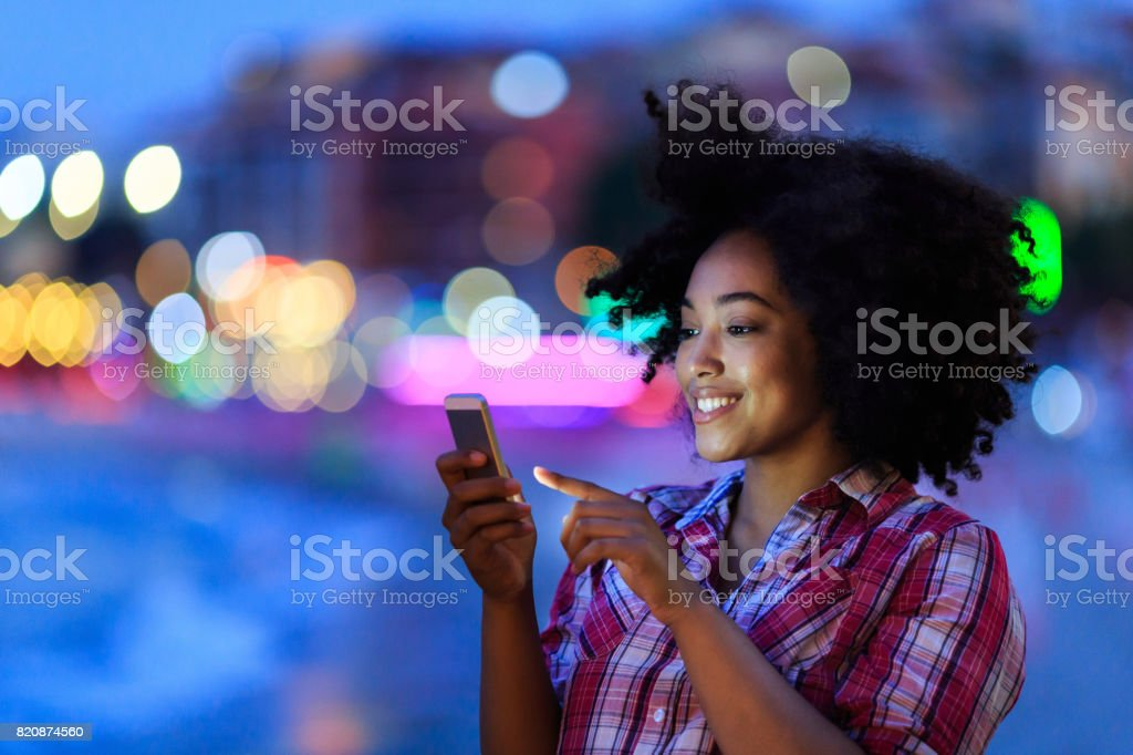 Attractive woman using smart phone at night on street stock photo