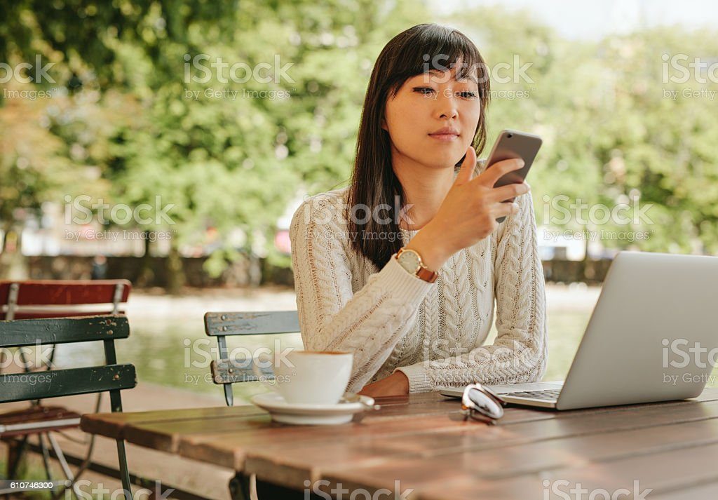 Attractive woman using smartphone at coffee shop stock photo