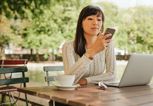 Attractive Woman Using Smartphone At Coffee Shop Stock Photo - Download Image Now