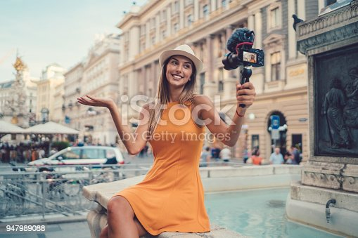 Young woman on a summer vacation vlogging from the city