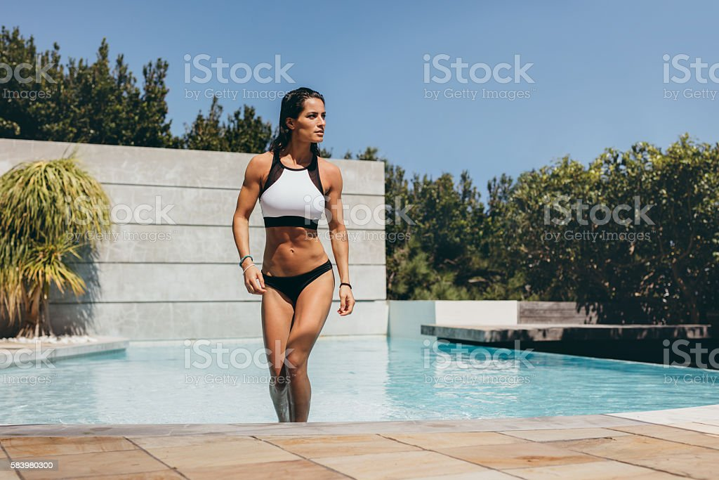 Attractive woman walking out of swimming pool stock photo