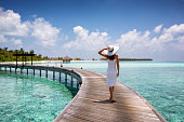 Attractive woman walks on a wooden jetty towards a tropical island in the Maldives