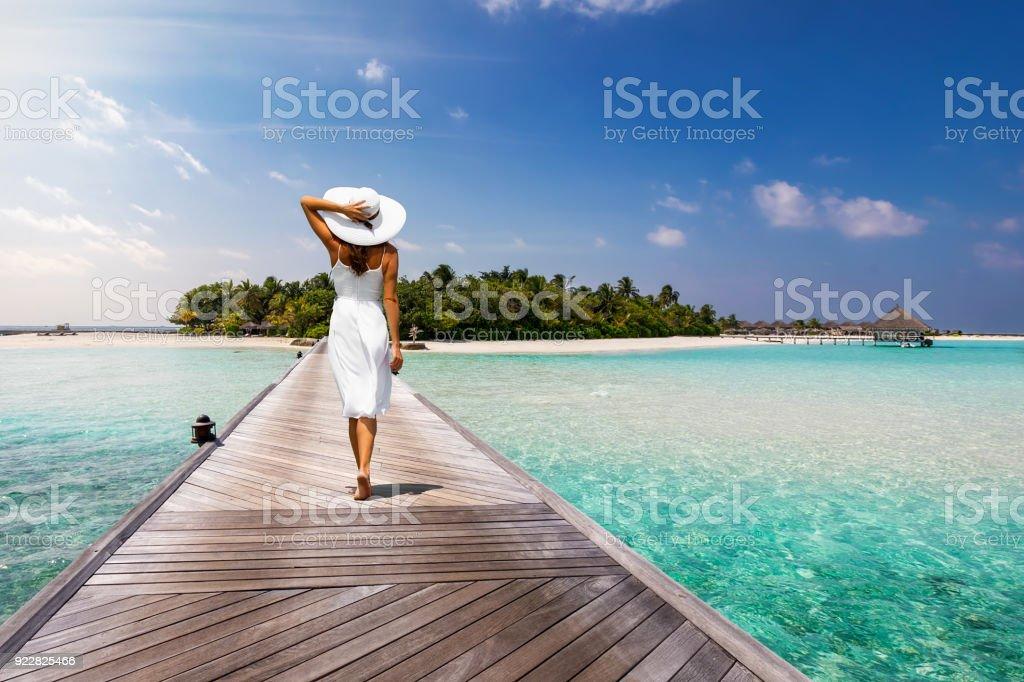 Jolie femme se promène sur une jetée en bois vers une île tropicale photo libre de droits