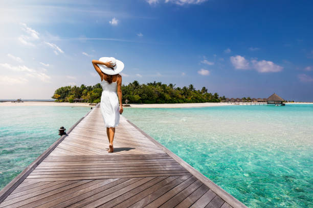 Attractive woman walks over a wooden jetty towards a tropical island stock photo
