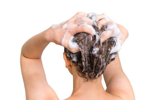 attractive woman washing hair with shampoo in shower - lavarsi i capelli foto e immagini stock
