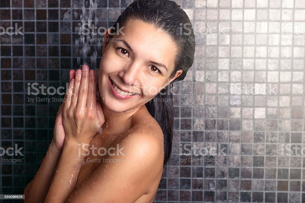 Attractive woman washing her hair in the shower stock photo