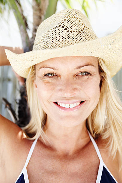 Attractive woman wearing a bikini smiling Closeup portrait of attractive mature woman in bikini smiling middle aged women in bikinis stock pictures, royalty-free photos & images