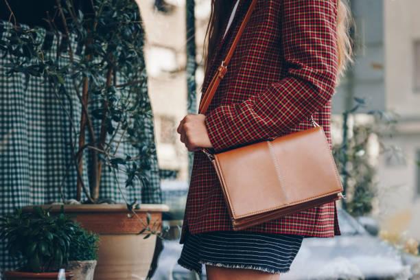 aantrekkelijke vrouw het dragen van een minirok, selectievakje geruite blazer en een lether bruine tote tas. fashion outfit perfect voor de herfst. stijl van het najaar van 2018. - men blazer stockfoto's en -beelden
