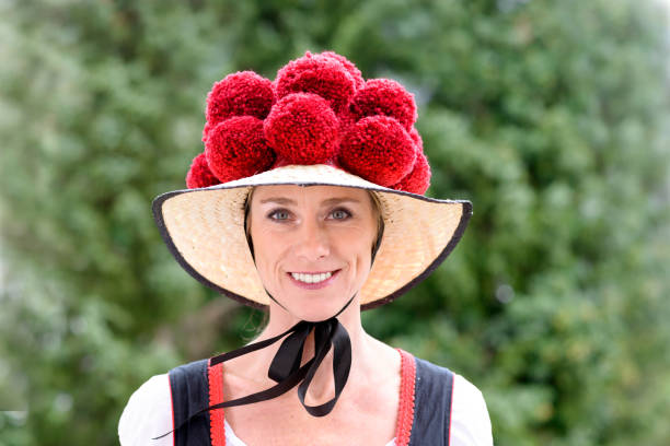 Attractive woman wearing a traditional Bollenhut Attractive young woman wearing a traditional Black Forest Bollenhut with its 14 pompoms as she smiles at the camera outdoors against greenery black forest stock pictures, royalty-free photos & images