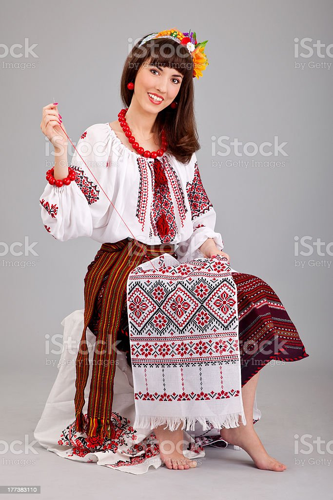 Attractive woman wears Ukrainian national dress is sewing royalty-free stock photo