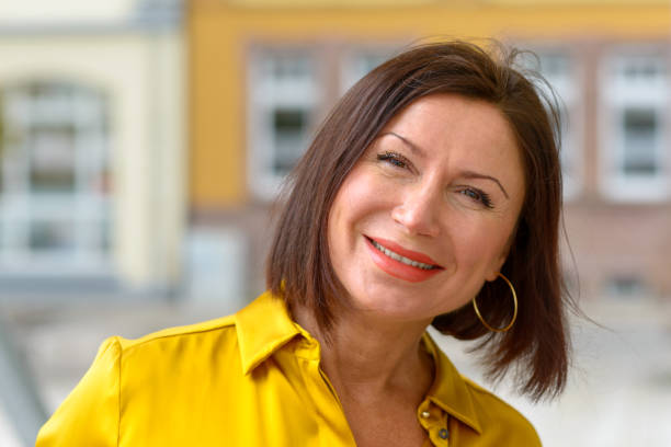 Attractive woman with a lovely warm friendly smile stock photo