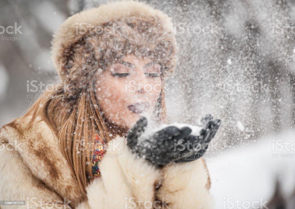 Attraktive Frau mit braunen Pelzmütze und genießen Sie den Winter Jacke. Seitlicher Blick auf modische blonde Mädchen posieren gegen Schnee bedeckte Brücke. Schöne junge Frau mit Wetter-outfit – Foto
