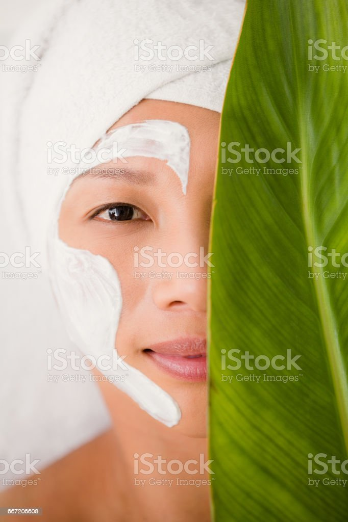 Attractive woman with cream treatment behind a leaf royalty-free stock photo