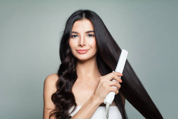 Attractive Woman with Curly Hair and Long Straight Hair Using Hair Straightener. Hair Problem and Haircare Concept Attractive Woman with Curly Hair and Long Straight Hair Using Hair Straightener. Cute Smiling Girl Straightening Healthy Brunette Hair with Flat Iron. Hair Problem and Haircare Concept straight hair stock pictures, royalty-free photos & images