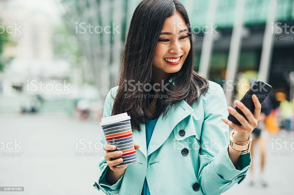 Attractive woman with phone and coffee stock photo