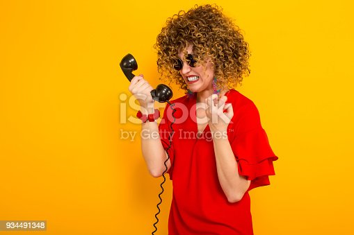 istock Attractive woman with short curly hair with phone 934491348