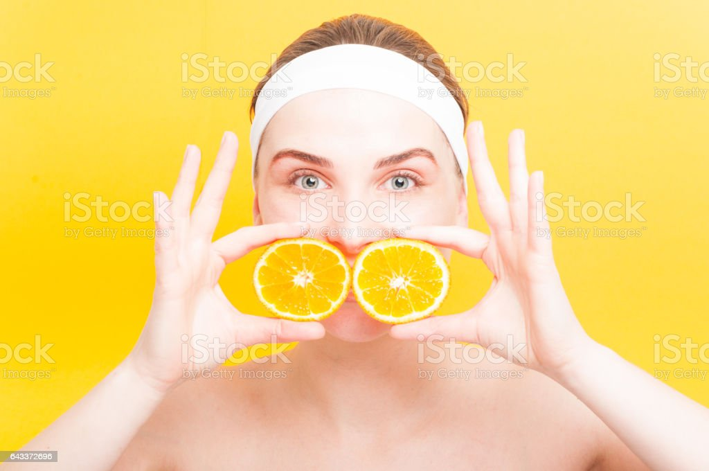 Attractive woman with two slices of orange fruit stock photo