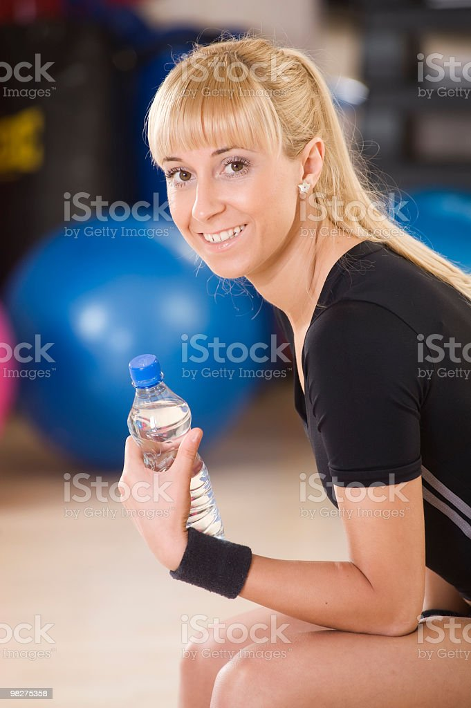 Attractive woman with water bottle in gym royalty-free stock photo