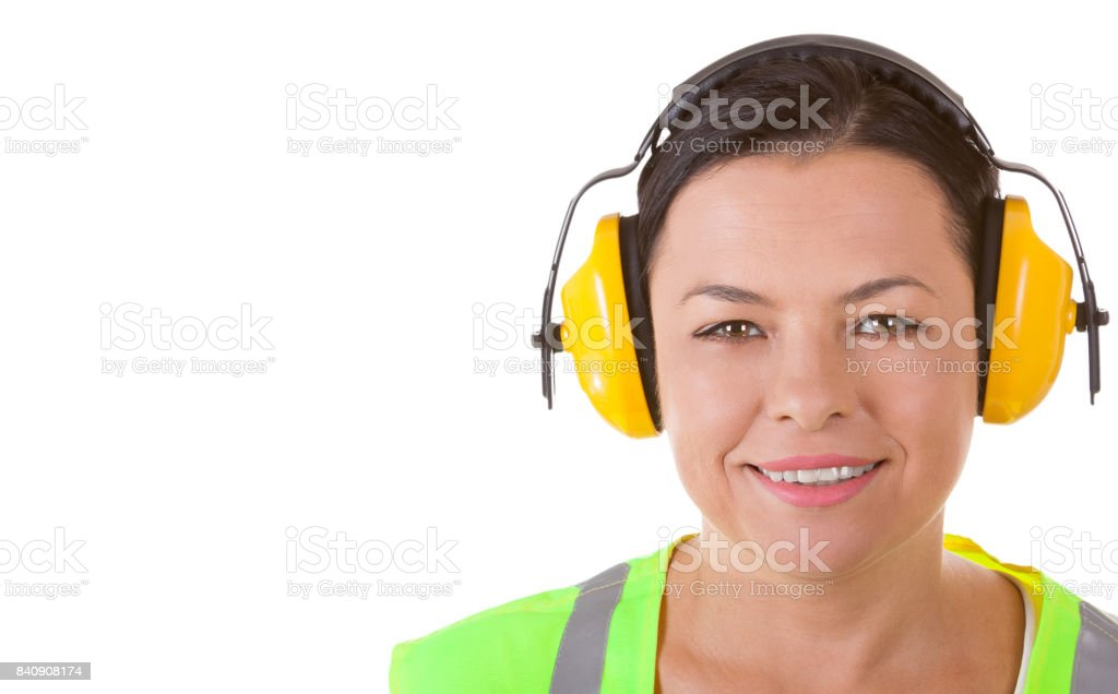 Attractive Woman Worker in Safety Jacket and Protective Ear Headphones with Copyspace for Yours Design stock photo
