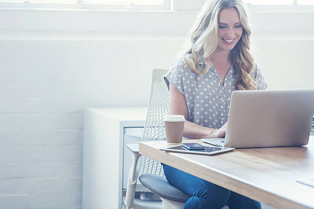 attraente donna che lavora su un computer portatile. - owner laptop smartphone foto e immagini stock