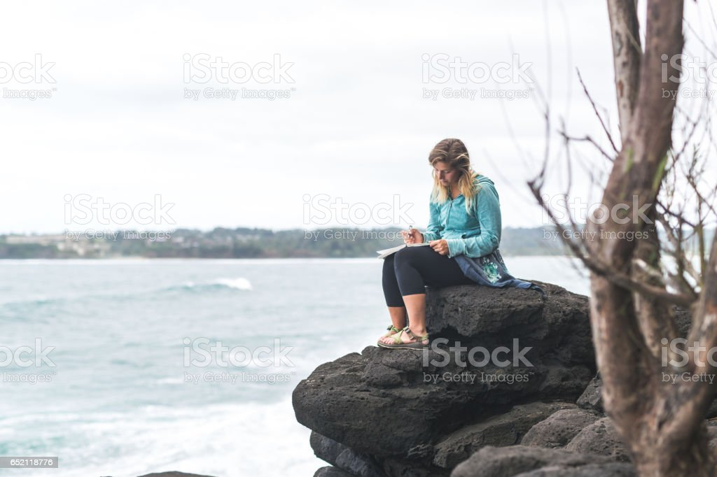 Attractive woman writing in journal on rock outcropping over Hawaiian coastline stock photo