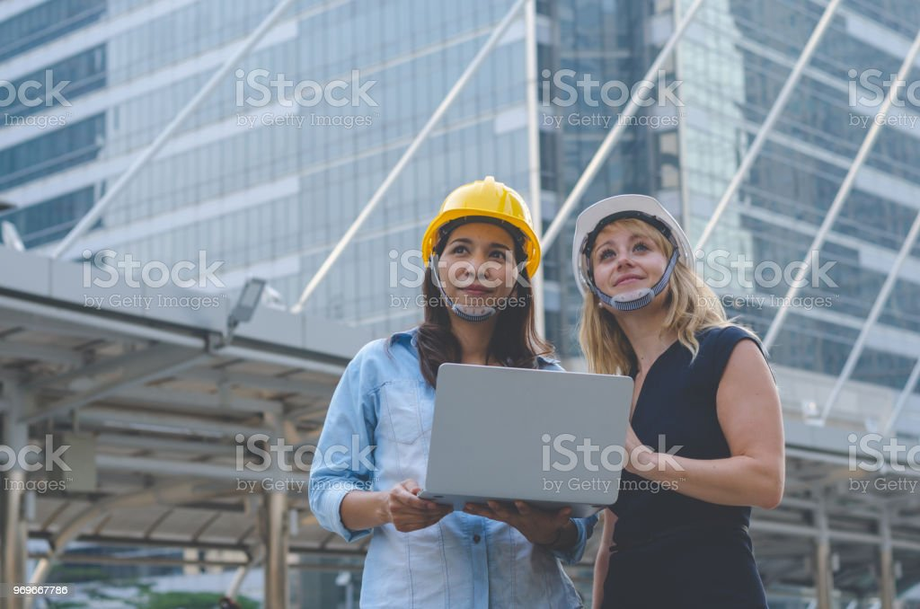 attractive women architecture and woman engineer together working at...
