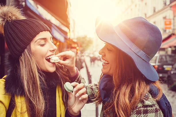 attraktive frauen essen pariser makronen - genießen französisch stock-fotos und bilder
