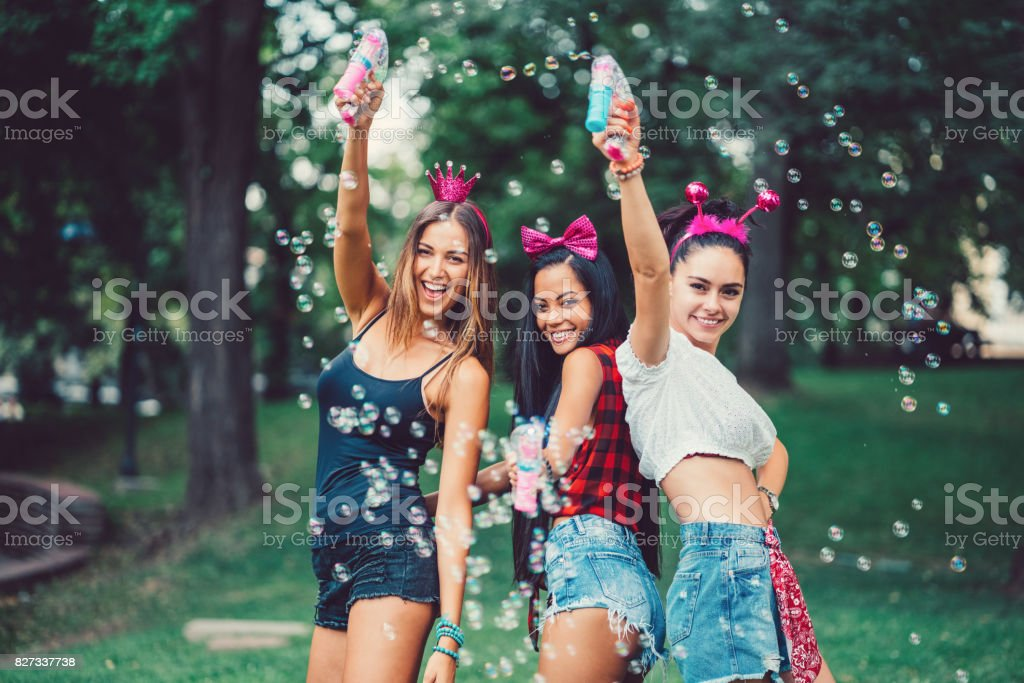 Attractive women making soap bubbles in the park stock photo