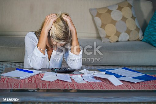 istock attractive worried and desperate blond woman calculating domestic money expenses doing paperwork and bank bills accounting with calculator suffering stress in financial problem and depression 981862904