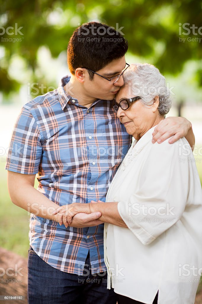 Attractive young adult man embracing his grandmother – Foto