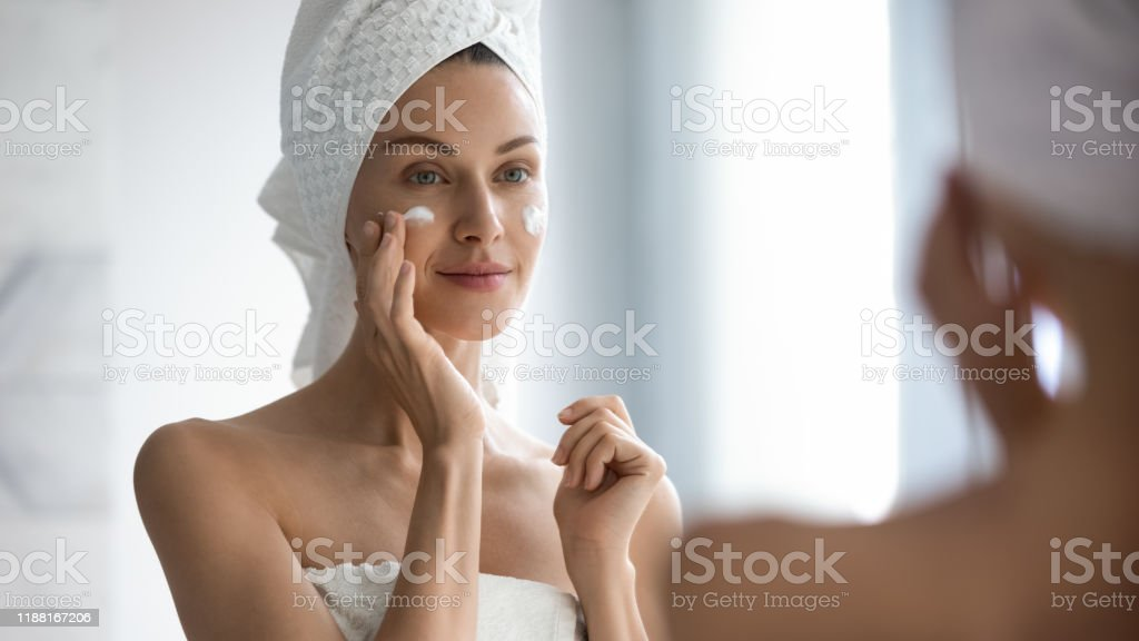 Attractive young adult woman applying facial cream looking in mirror - Foto stock royalty-free di Accudire