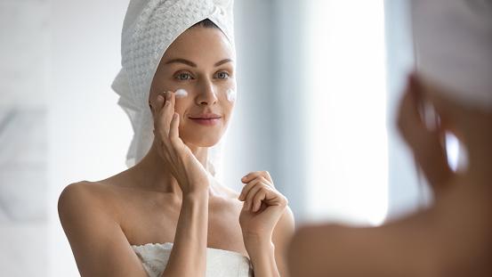 Attractive Young Adult Woman Applying Facial Cream Looking In Mirror - Fotografie stock e altre immagini di Accudire