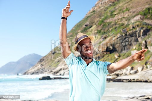 istock Attractive young african man having fun at the beach 535468232