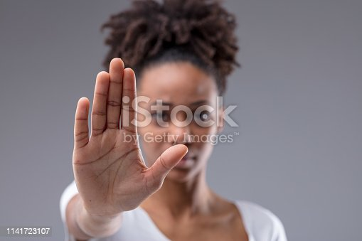 Attractive young African woman giving a halt or stop gesture with focus to the palm of her hand over a grey studio background