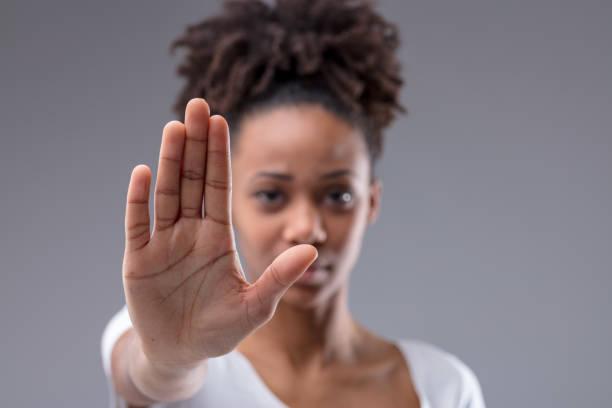 atractiva joven africana dando un gesto de detención - dureza fotografías e imágenes de stock
