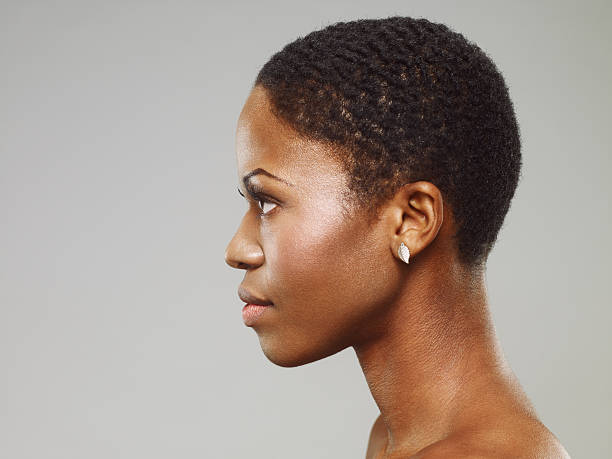 Attractive Young African Woman Side view portrait of an attractive young african woman with short hair. side view stock pictures, royalty-free photos & images