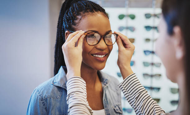 attractive young african woman selecting glasses - optometrist stock pictures, royalty-free photos & images