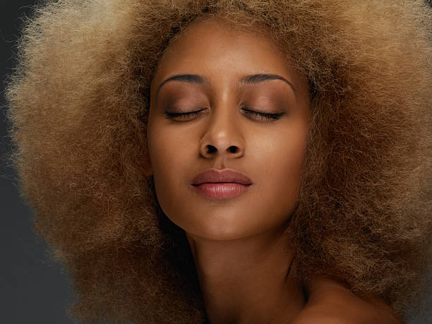 attractive young african woman with curly hair stock photo