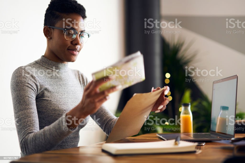 Attractive young afro american businesswoman receiving from post envelope with documentation for project earning money online, professional designer in eyewear packing working papers for mailing stock photo