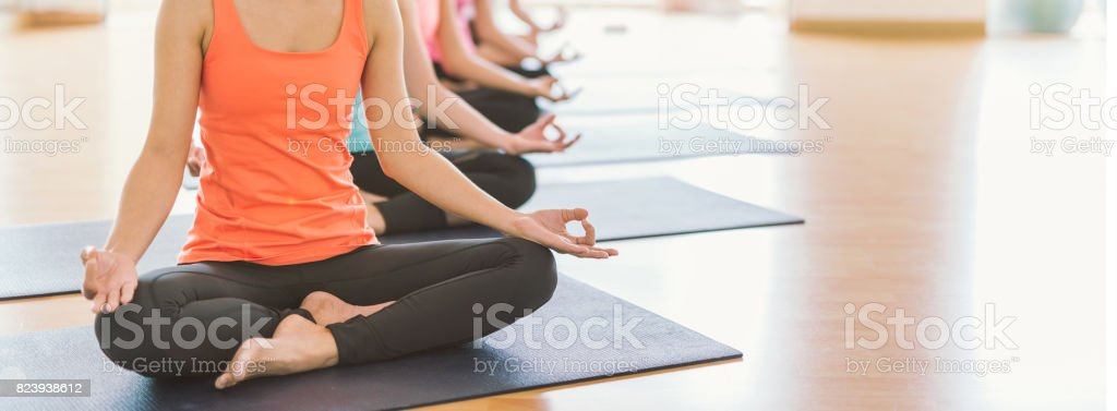 Attractive young Asian woman group exercising and sitting in yoga lotus position in yoga classes stock photo