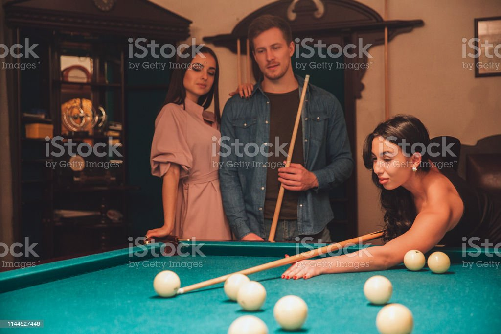 Attractive young asian woman play billiard game. She looks noce and...