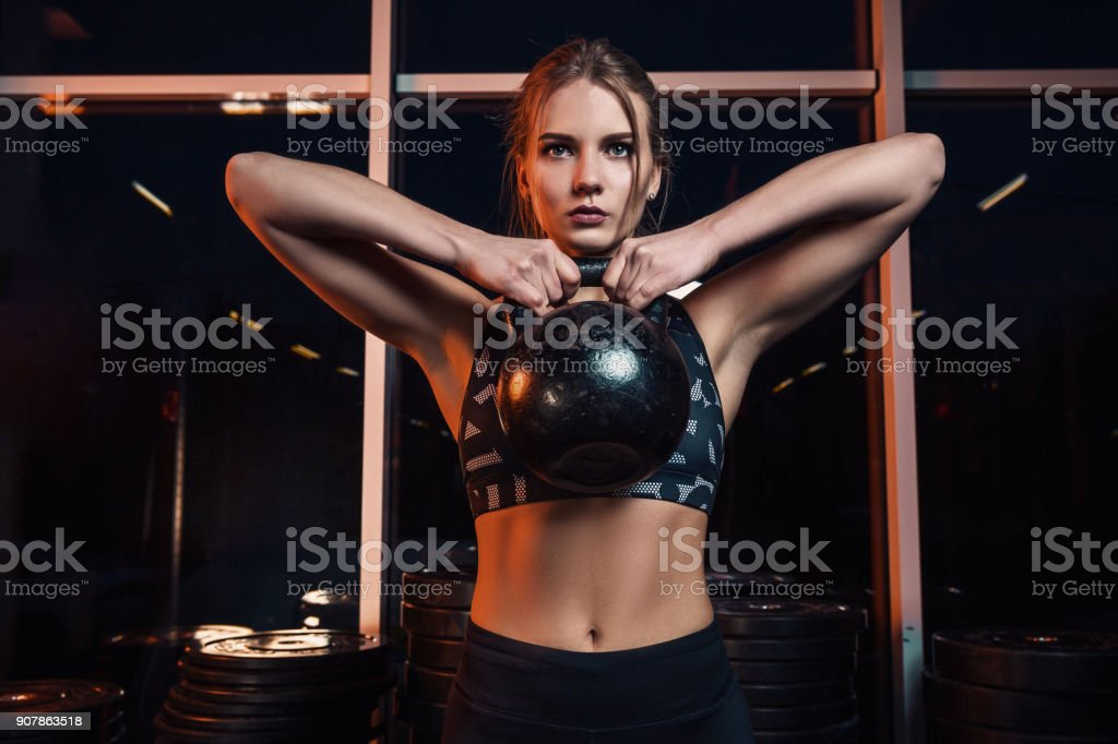 Attractive young athlete with muscular body exercising gym. Woman in sportswear doing gym workout with kettle bell at the gym stock photo