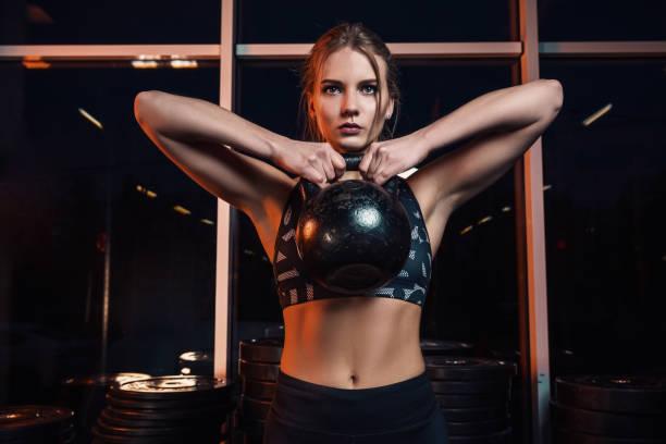 Atleta joven atractiva con cuerpo musculoso ejercicio crossfit. Mujer en ropa deportiva haciendo entrenamiento de crossfit con la campana de la caldera en el gimnasio - foto de stock