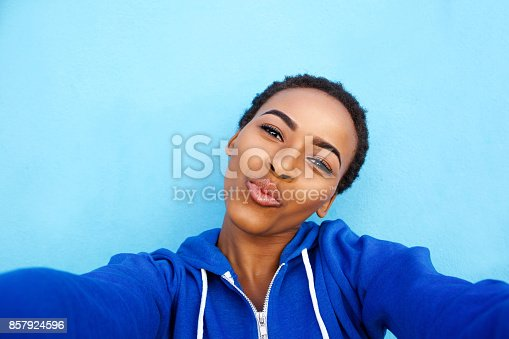 istock attractive young black woman kissing when taking selfie 857924596