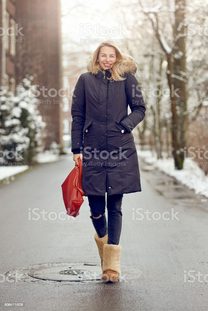 Attractive young blond woman in warm winter coat stock photo