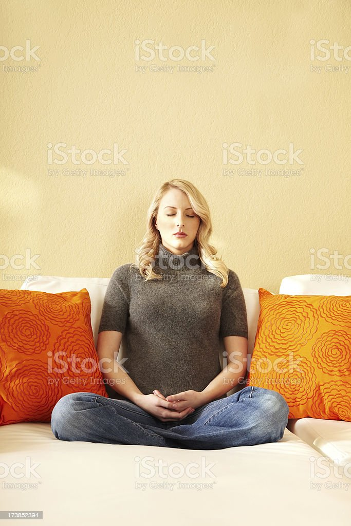 Attractive Young Blond Woman Meditating on Her Couch royalty-free stock photo