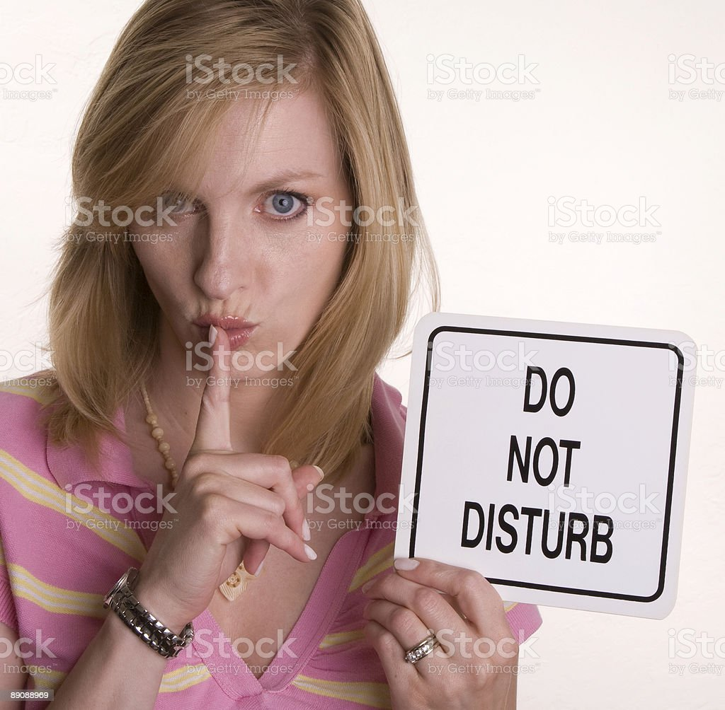 Attractive young blonde woman holds up 'Do Not Disturb' sign 免版稅 stock photo